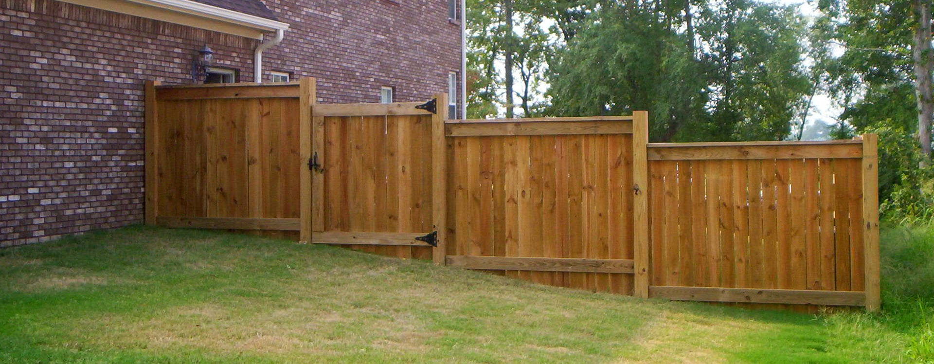 wood fence on a sloped yard - Tupelo